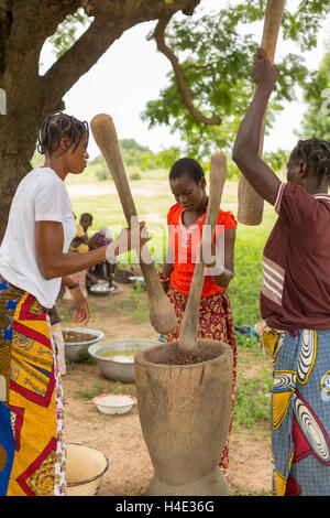 Shea nuts are pounded by women as part of the shea butter and oil production process in Réo, Burkina Faso, West - Stock Photo