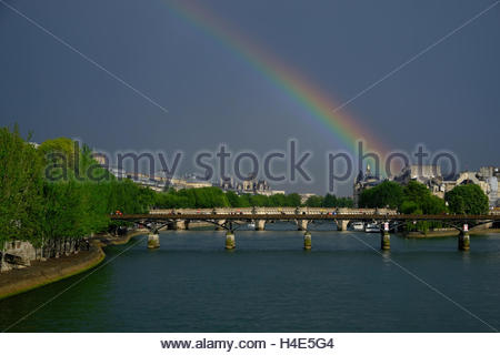 A colorful rainbow appears after an afternoon rain over the Seine River near the Louvre. - Stock Photo