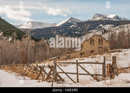 Remains of a twenty-stamp gold mill built in 1883 in Montana on a winter day with the Tobacco Root Mountains in - Stock Photo