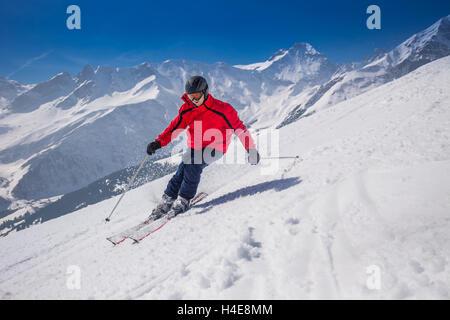 Young happy man skiing in Lenzerheide ski resort, Switzerland. - Stock Photo