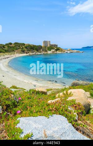 Beach with azure sea and castle in the background near Porto Giunco port, Sardinia island, Italy - Stock Photo