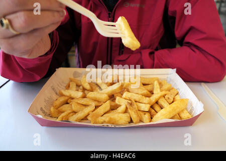 A lady eating a portion of freshly cooked fish and chips from a Harry Ramsden fish and chip shop - Stock Photo