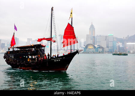 Red sail junk boat in the Victoria Harbour, Hong Kong - Stock Photo