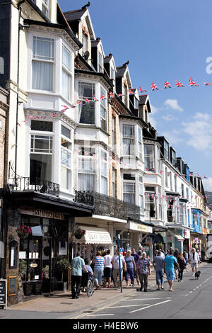 Visitors walking outside shops and cafes on The Quay, Ilfracombe, North Devon UK - Stock Photo