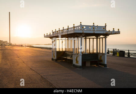 Ornate regency seating shelter with benches in on Brighton / Hove seafront promenade with sunrise in the background - Stock Photo