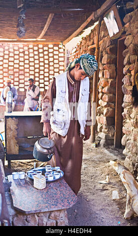 The young Bedouin pours tea to offer it to the tourists, Africa Egypt Sahara Hurghada - Stock Photo