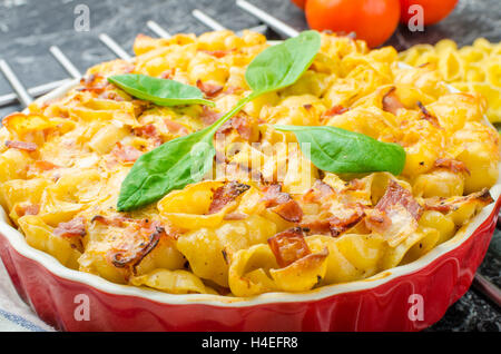 Baked homemade pasta with leeks, bacon and cream, spinach and fresh tomatoes from the garden - Stock Photo