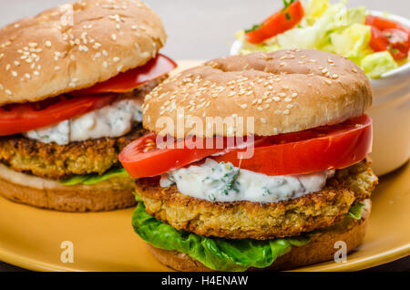 Vegetarian chickpea burger, tomato and dip of herbs, garlic and yogurt and salad with cherry tomatoes - Stock Photo
