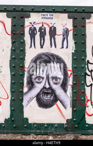 Mural representing man covering his face with his hands and eyes drawn on them and four man elegantly dressed with - Stock Photo