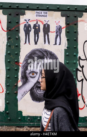 Muslim woman wearing a traditional black hijab or veil walking in front of a wall with mural in Brick lane - Stock Photo