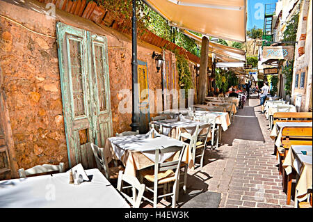 The cafe is located in the narrow lane, walls of houses are decorated with old doors with old doors, Chania Crete - Stock Photo