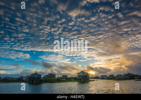Sun is rising from the clouds over Avon North Carolina on the Hatteras island of Outer Banks OBX reflecting in Pamlico - Stock Photo