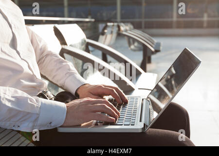 Businessman in airport waiting lounge typing on laptop - Stock Photo