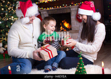 Family exchanging gifts in front of fireplace at Christmas tree - Stock Photo