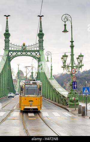 Yellow tram on the Liberty Bridge or Freedom Bridge in Budapest, Hungary. - Stock Photo