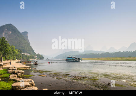 Pier for boats in the tourist town Yangshuo on the banks of Li river in China - Stock Photo