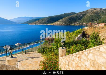 Walkway to to sea and mountain view on coast of Kefalonia island in Agia Efimia village, Greece - Stock Photo