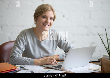 Portrait of a smiling student girl at desk with laptop - Stock Photo