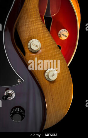 Close up view of control knobs on different guitars on gray background - Stock Photo