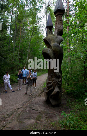 A local guide leads visitors on a tour of the Hill of Witches, site of an assemblage of more than 80 totem-like - Stock Photo