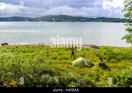 Man standing near tent after camping in Sweden (Orust) - Stock Photo