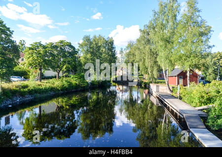 Lakehouse reflecting in the lake in a forest, Sweden - Stock Photo