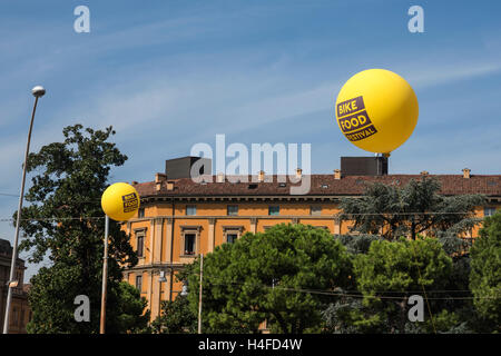 Huge bright yellow balloons  above  the roofs of the city, Bologna, Italy, Europe - Stock Photo