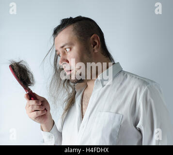 a man looking at a hairbrush with a loosing hair - Stock Photo