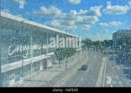 Shattered concept vision of a main road & Tesco Store in Slough Berkshire UK as seen through a crazed broken glass - Stock Photo