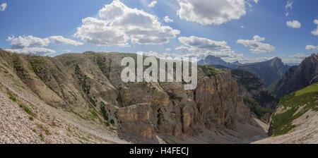 Panoramic mountain cliff to the Passo Pordoi gap in the italic Dolomites. - Stock Photo
