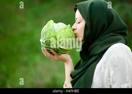 Muslim Vegan Woman with Veil Kissing a Savoy Cabbage - Stock Photo