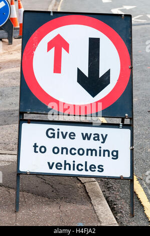 A temporary road sign warns driver to give way to oncoming vehicles. - Stock Photo