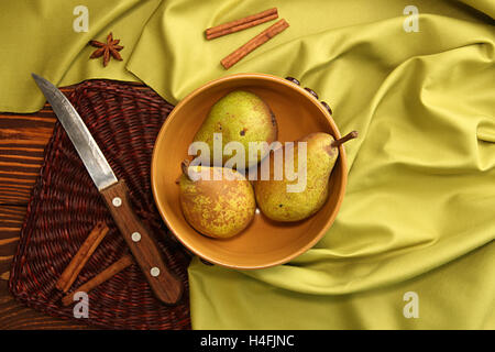 Homegrown pears from rural garden in ceramic bowl on napkin and cinnamon sticks and stars aniseed tree on fabric - Stock Photo