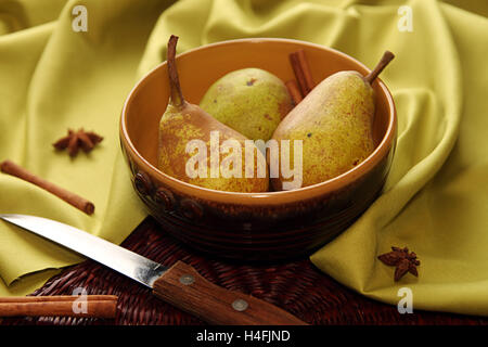 Homegrown pears from rural garden in ceramic bowl on napkin and cinnamon sticks and stars aniseed tree on cloth - Stock Photo