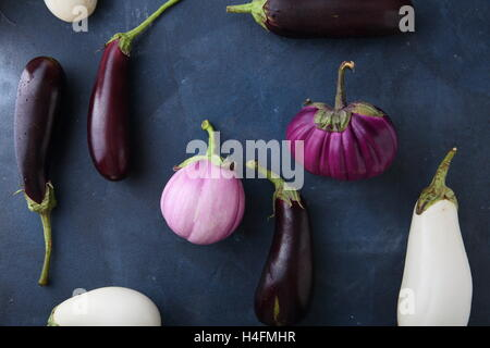 Fresh eggplants on slate, food top view - Stock Photo