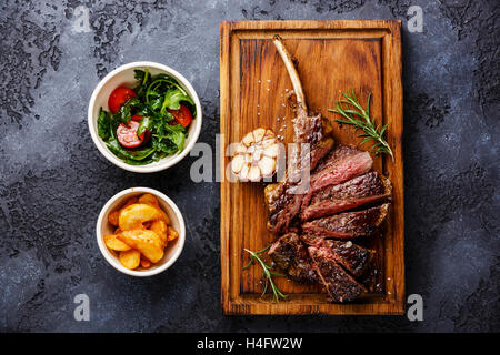 Sliced grilled Steak on bone Veal rib with potato wedges and salad with tomatoes and arugula on dark background - Stock Photo