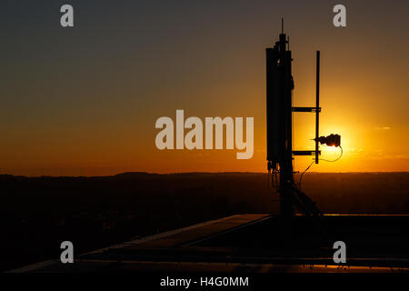 Mobile communications mast/antenna atop a tall building, against sunset. In Nottingham, England - Stock Photo