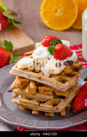 Belgian waffles with chocolate, bananas and strawberries, syrup-drenched - Stock Photo
