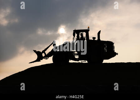 Shovel Silhouette, Wheel loader rolling a silage heap at a farm during twilight with full moon. - Stock Photo