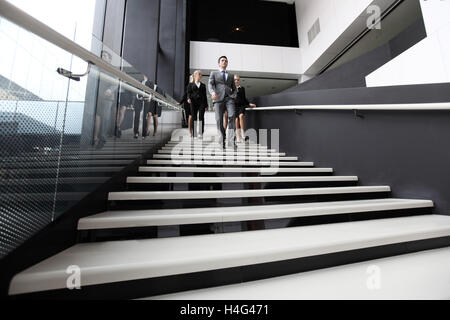 Business people walking down the steps of stairs - Stock Photo