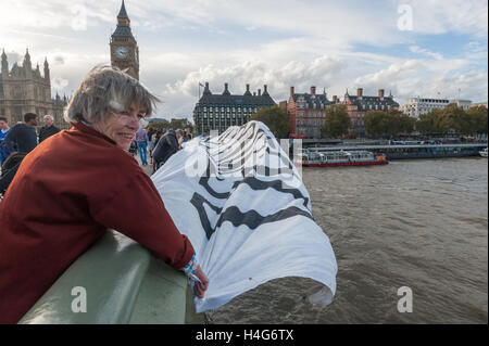 London, UK. 15th October 2016. London Action Network dropped a banner from Westminster Bridge warning against the - Stock Photo