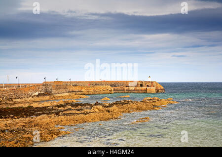A view of the rocky shoreline and entrance to the harbour at Banff, Aberdeenshire, Scotland, United Kingdom. - Stock Photo
