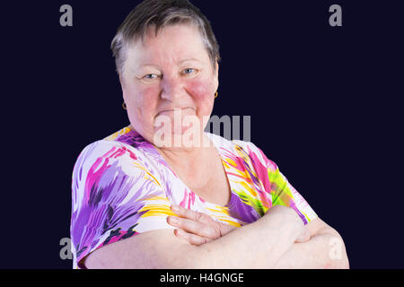 Portrait of disappointed senior woman with grimacein photo studio isolated on dark blue background - Stock Photo
