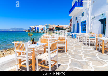 Chairs with tables in typical Greek tavern in Little Venice part of Mykonos town, Mykonos island, Greece - Stock Photo