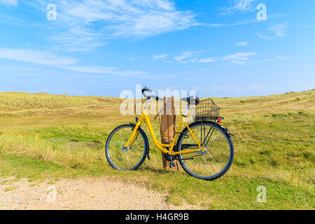 SYLT ISLAND, GERMANY - SEP 6, 2016: yellow bike parked against a field fence in countryside landscape of Sylt island - Stock Photo