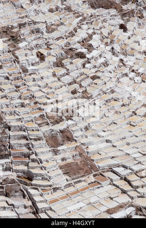 Looking down from a neighboring peak on hundreds of salt plots at the Maras salt mines near Cusco, Peru - Stock Photo