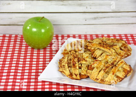 apple pie cookies with green apple on red and white checkered tablecloth - Stock Photo