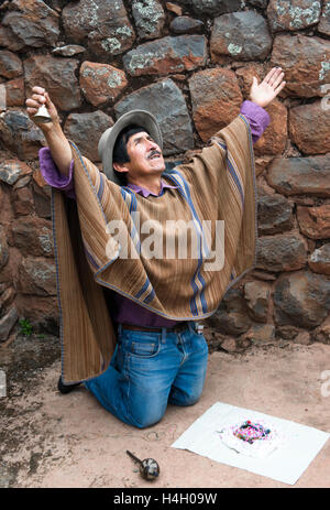 Peruvian Shaman doing coca leaf blessing for Pachamama in mountaintop ruins of Tipon, Peru in the Sacred Valley. - Stock Photo