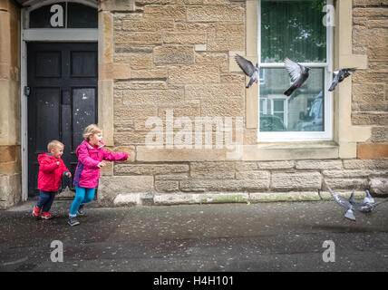 Little boy and girl chasing pigeons in front of a home in Edinburgh - Stock Photo