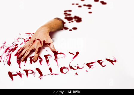 Bloody cut hand and Happy halloween written with red human blood on white background. - Stock Photo